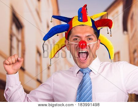Happy handsome young businessman with a red clown nose and colorful harlequin hut in his head.