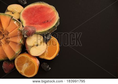 Various fruits packed in plastic film on black background. With copy space