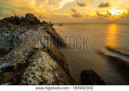Long exposure of sea and rocks during evening sunset at Labuan island,Malaysia.The constant waves around the rocks blur creating a dreamy effect. that constrasts to the jagged sharpness of the rocks.