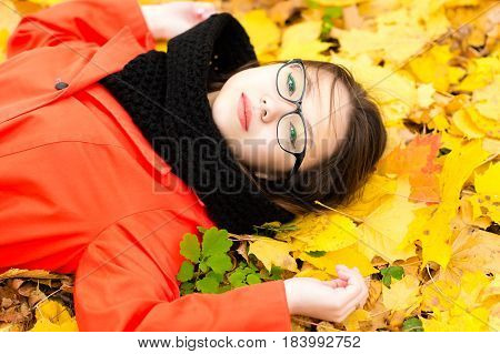 attractive girl with glasses lying on leaves