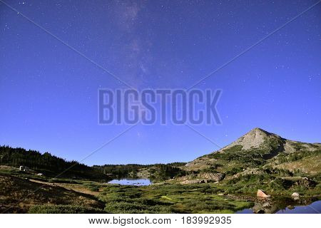 Long Exposure Night Shot Of The Medicine Bow Mountains Of Wyoming, Alpine Lake, And Stars