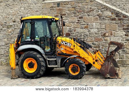 Cornwall, Uk - April 3 2017: Yellow Jcb Tractor Or Digger Parked Next To A Stone Wall