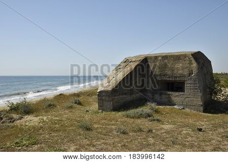 Foxhole on the beach with sea and blue sky in background picture from the North of Cyprus.
