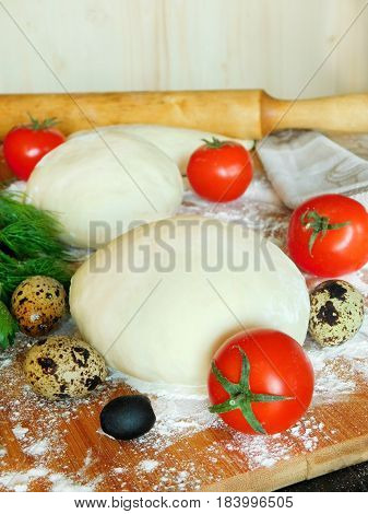 Yeast dough surrounded by tomatoes, fresh green and quail eggs is being prepared for baking