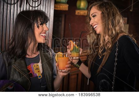 Two Fashion Woman Drinking Orange Alcohol Cocktail In The Pub