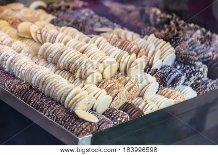 Various flavors of white and dark chocolate in large tray seen through shop window selective focus