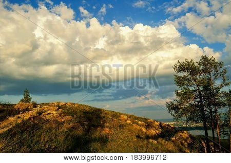 Summer mountain landscape- dramatic clouds over the top of the Sugomak mountain in Southern Urals Russia.Top of the mountain -summer mountain background.Sunny summer clouds over the mountain. Ural mountains