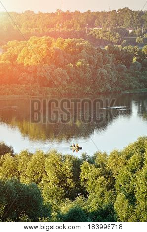 Summer water landscape with fisherman sailboat on the summer river lit by soft morning summer sunlight. Aerial landscape with summer river - summer landscape view. Sunny summer background with forest river in the sunrise