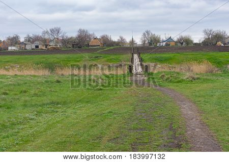 Pedestrian path through spring meadow to old foot-bridge over small river Tomakivka in Topyla village central Ukraine