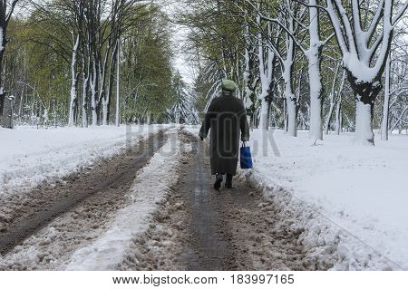 Dnepr Ukraine - April 19 2017: Lonely woman walking om a snowy street after powerful April snow storm