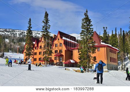 Ski resort Sheregesh Green mountain Mountain Shoria Kemerovo region Russia - March 192017: Beautiful sunny mountain landscape with skiers and snowboarders near the hotel.