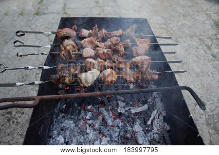 kebab prepares on the fire outdoors. Cooking process. Roasted meat barbecue on the grill. Caucasian dish skewers