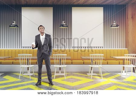African American businessman standing in a cafe with posters hanging on a gray wooden wall yellow sofa square tables and white chairs near them. 3d rendering mock up toned image