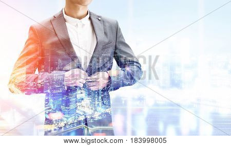 Close up of an unrecognizable businessman buttoning his suit standing against a night city panorama. Mock up toned image double exposure