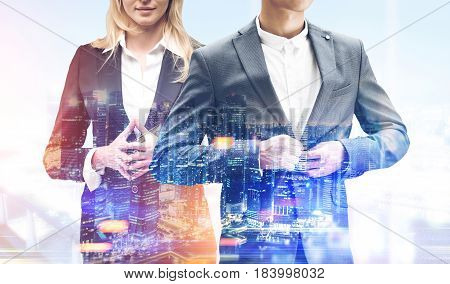 Unrecognizable blond businesswoman and a businessman buttoning his suit are standing against a foggy city panorama. Toned image double exposure