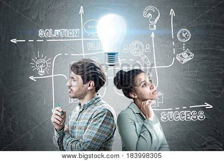 Portrait of a man and an African American woman standing back to back near a blackboard with a business scheme drawn on it and a blue light bulb glowing above their heads.