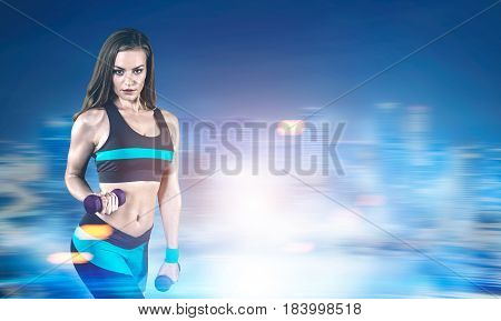 Portrait of a young woman wearing black and blue sportswear and holding dumbbells standing against a blurred night city background. Mock up toned image