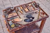 work table with small shoes for children and old tools of the artisan shoemaker for repair and finishing shoe poster