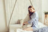 young woman in pajama wake up in the morning in cozy scandinavian bedroom and sitting on bed with white bedlinen. Casual lifestyle in modern interior poster