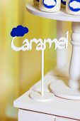 Candy bar on baby's christening party with a lot of different candies and beverages. Decorated in blue colors clouds theme indoor poster