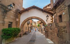 Barcelona, Spain - Nov 2nd, 2013:  Tourism in Barceloneta - tourists & people walk down a street of small town on interior of Barcelona.  Charming cafes, shops, & brick archway over a cobblestone street.