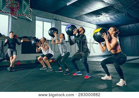 Functional Fitness Workout At The Gym With Medicine Ball. The Group Of Young People During Training