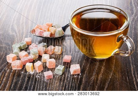 Cubes Of Multicolor Rakhat-lukum In Spoon And Scattered On Table, Cup Of Tea On Dark Wooden Table