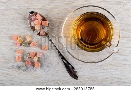 Cubes Of Multicolor Rakhat-lukum In Metallic Spoon, Scattered Rakhat-lukum, Cup Of Tea On Saucer On