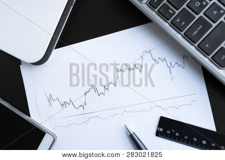 Financial Graph On White Paper With Notebook Laptop Computer And Others Office Items On Working Tabl