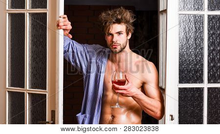 Sexy Attractive Macho Tousled Hair Coming Out Through Bedroom Door. Man With Sexy Torso Drink Wine.