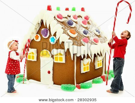 Young brother and sister building a giant gingerbread house together.