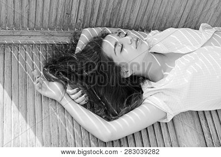 Heat Concept. Woman Brunette Chilling While Stands Near Jalousie, Stripes Of Sunlight And Shadow On
