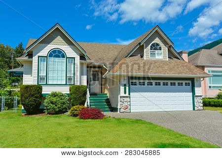 Suburban House In British Columbia For Sale. Big House With Wide Garage Door, Concrete Driveway, And