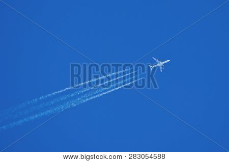 Jet Aircraft Flying At High Altitude With Contrails.