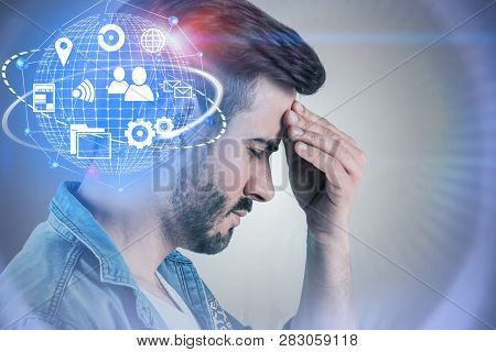Stressed Bearded Man In Jeans Shirt With Serious Headache Standing Near White Wall With Internet Ico