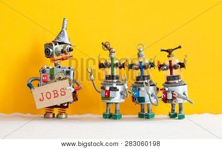 Three Robots Want To Get A Job And Stand In A Queue For An Interview. Robot Director With Cardboard