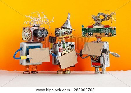 Comical Robots With A Cardboards Mockups. Creative Design Robotic Toys Holding A Blank Empty Paper P