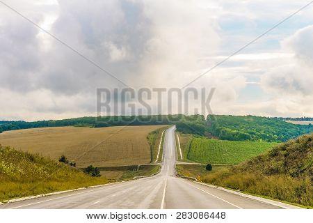 Slope Rural Asphalt Road With Marking. Summer Countryside Road To The Cloudy Horizon. Belgorod Regio