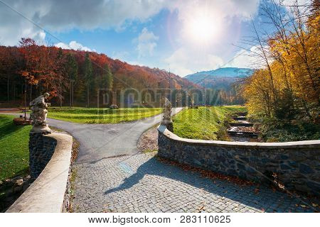 Park Among Mountain In Autumn. Trees In Colorful Foliage, Vivid Grassy Green Lawns. Walking Path To