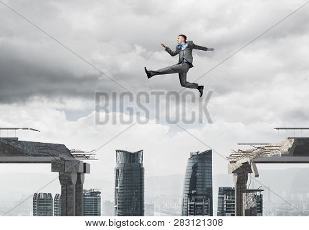 Businessman Jumping Over Gap In Concrete Bridge As Symbol Of Overcoming Challenges. Dark Sky And Cit