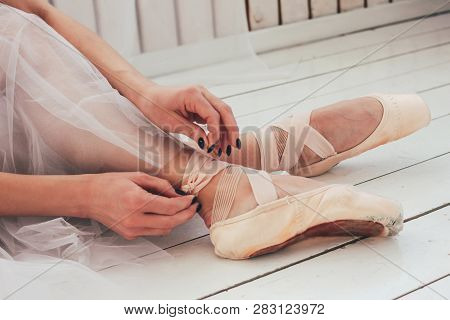 The Authentic Ballerina Ballet Dancer Sitting On The Floor And Tying Pointe Shoes, Close Up