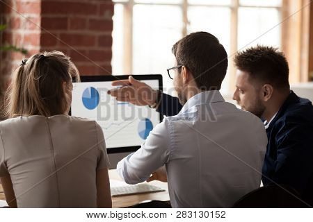 Rear View At Business Analysts Employees Talking Discussing Work Results