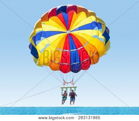 Happy Couple Parasailing In Turkey Beach In Summer. Couple Under Parachute Hanging Mid Air. Having F