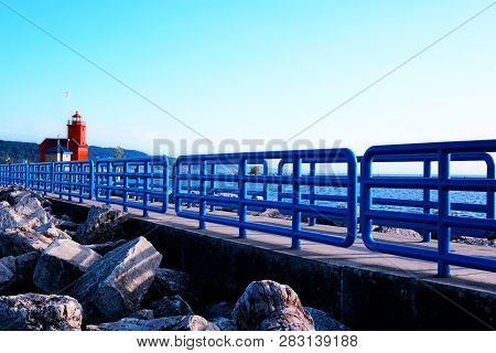 Blue Fences And Big Stones On The Pier Near Big Red Lighthouse At The Holland. Big Boulders Near The