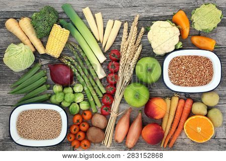 High fibre food for a healthy diet with fresh vegetables and fruit, whole grains and wheat sheaths. High in antioxidants, anthocyanins, vitamins and minerals. Top view on rustic wood.
