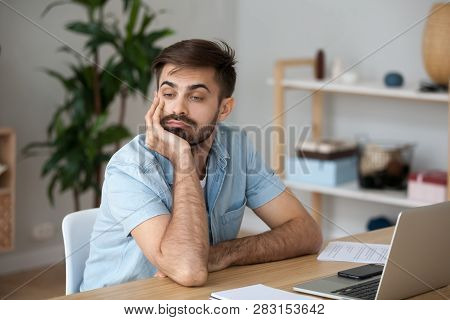 Tired Worker Wasting Time At Workplace Distracted From Boring Job