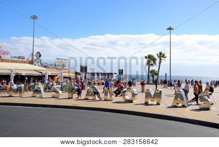 MASPALOMAS, SPAIN - JANUARY 23, 2019: A view of the promenade of Playa del Ingles, in Maspalomas, Gran Canaria, in the Canary Islands, Spain, a popular winter beach destination for European people