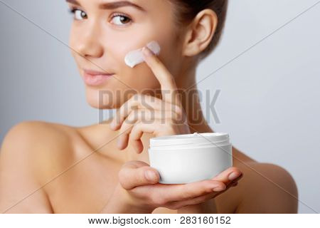 Woman Face Skin Care. Portrait Of Attractive Young Female Applying Cream  And Holding Bottle. Closeu