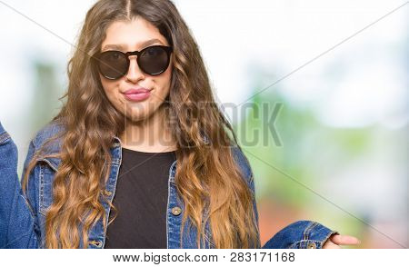 Young beautiful woman wearing sunglasses clueless and confused expression with arms and hands raised. Doubt concept.