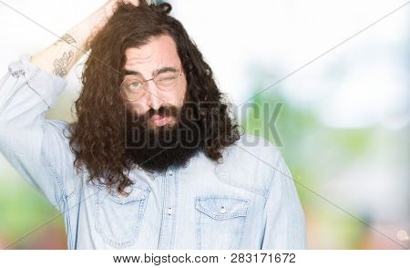 Young hipster man with long hair and beard wearing glasses confuse and wonder about question. Uncertain with doubt, thinking with hand on head. Pensive concept.
